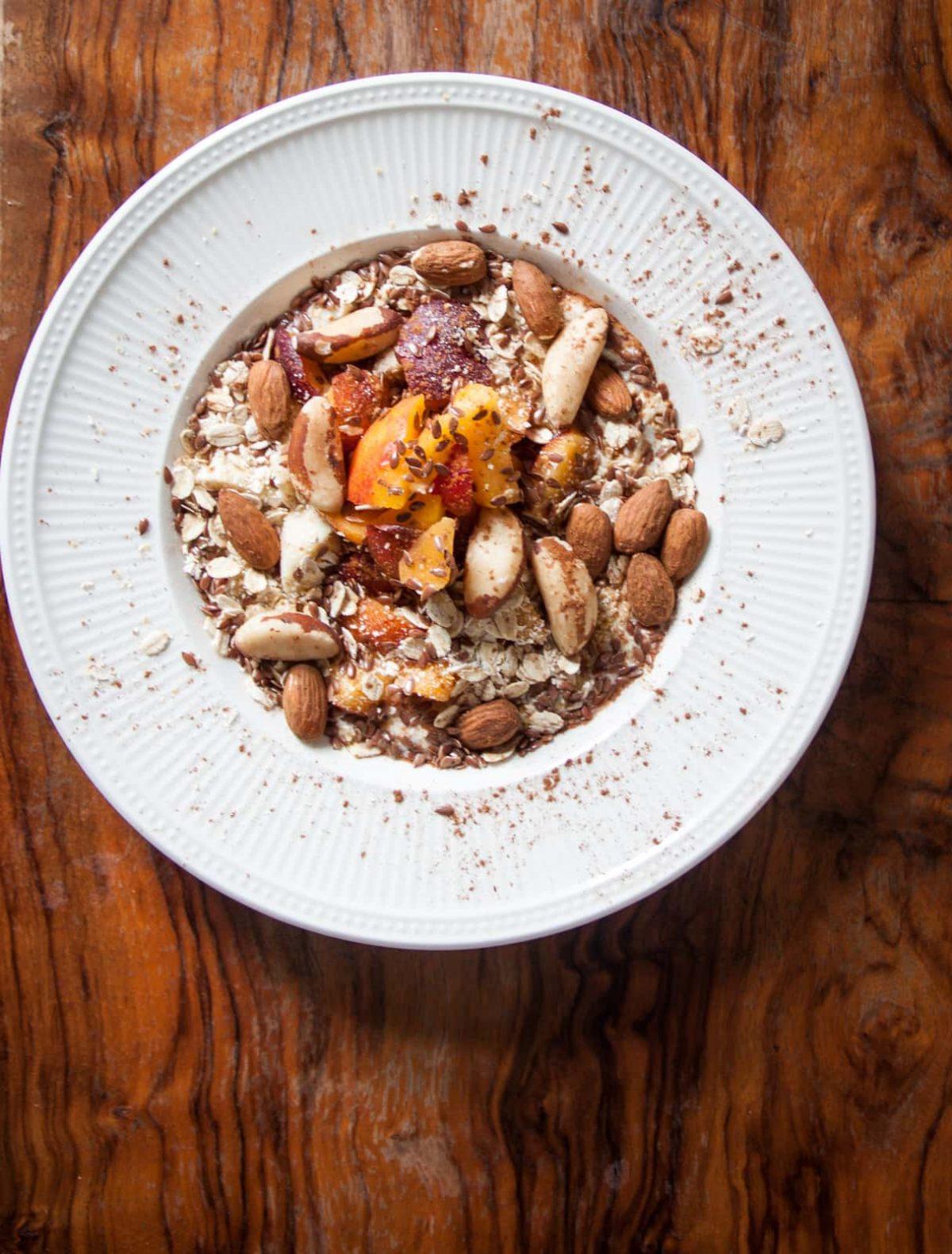Een bord havermout met yoghurt, fruit, noten op tafel