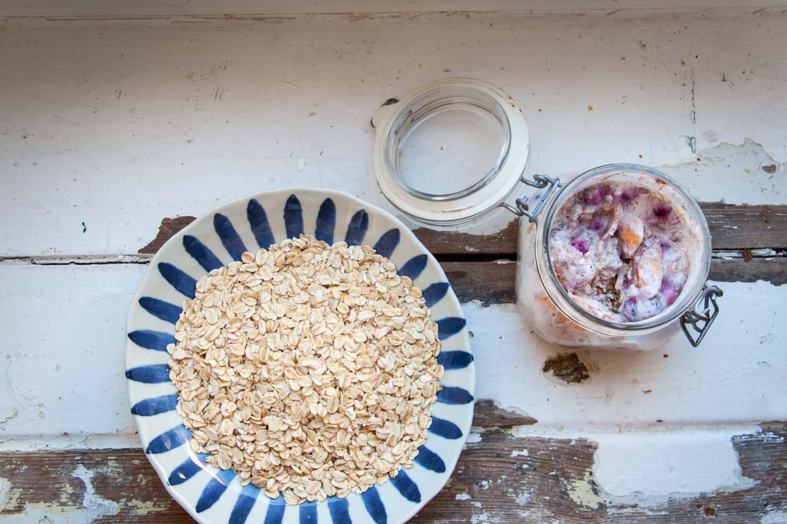 Overnight oats met rood fruit en perzik en een bord met havermout